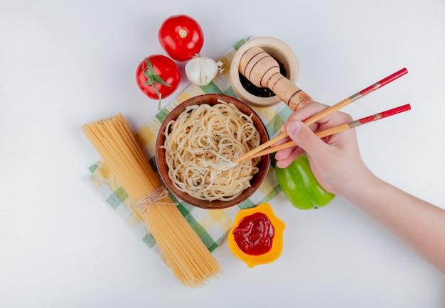 Bovenaanzicht van hand met stokjes en macaroni pasta in kom met tomaten zwarte peper ketchup knoflook peper en vermicelli op geruite doek en wit