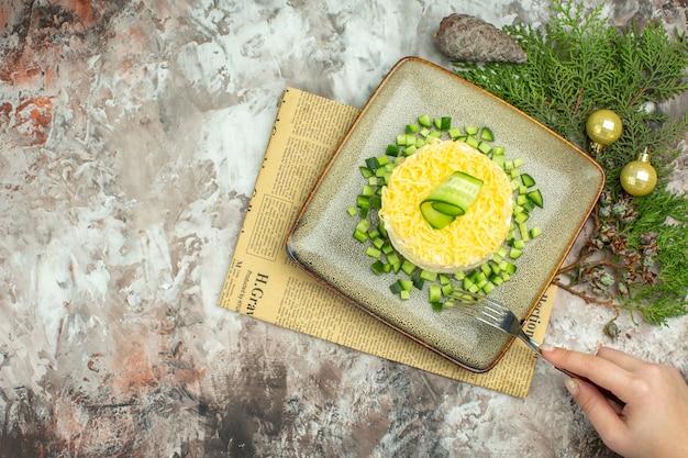Bovenaanzicht van hand met vork op smakelijke salade geserveerd met gehakte komkommer en mesvork op een oude krant