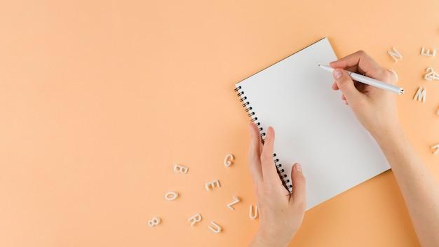 Bovenaanzicht van hand schrijven in notitieblok op bureau met kopie ruimte