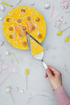 Bovenaanzicht van hand snijden cakeplak met verjaardagsdecoratie
