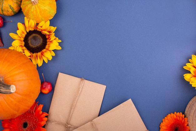 Bovenaanzicht van handcraft geschenkdoos met gele en oranje bloemen en pompoenen op blauw