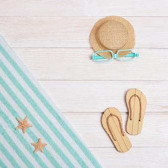 Bovenaanzicht van handdoek, strandslippers en hoed