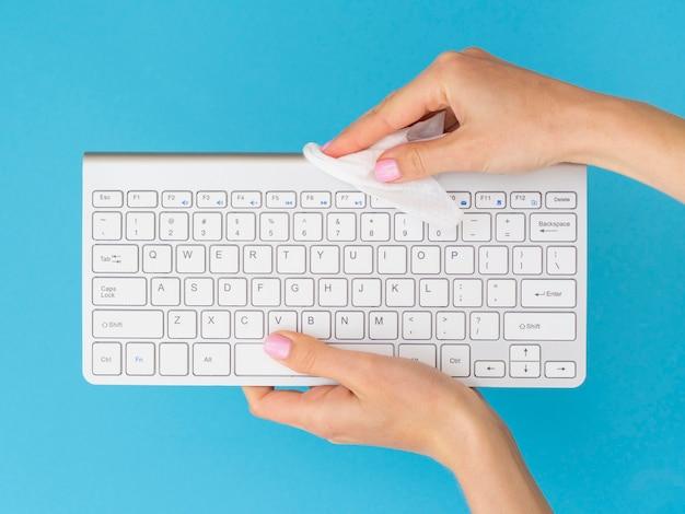 Bovenaanzicht van handen desinfecteren toetsenbord