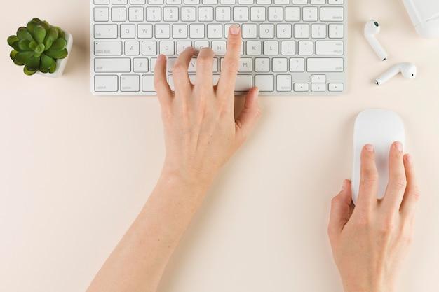 Bovenaanzicht van handen die op toetsenbord typen en muis op bureau gebruiken