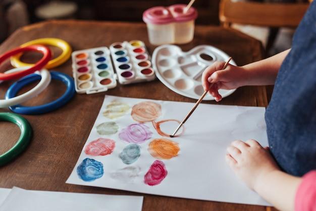 Bovenaanzicht van handen en penseelverf aquarel gouache