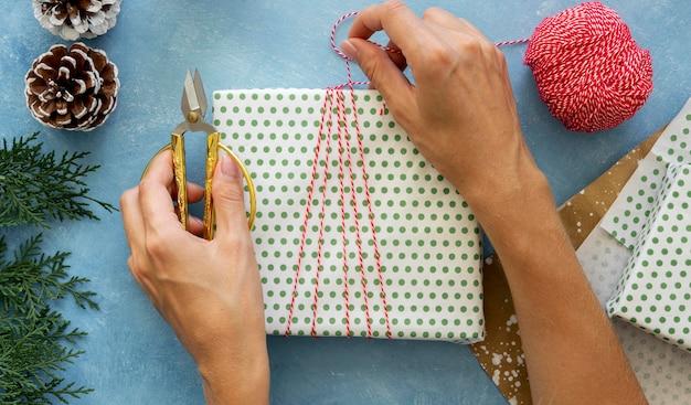 Bovenaanzicht van handen inwikkeling string rond kerstcadeau
