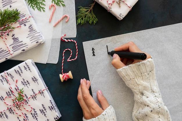 Bovenaanzicht van handen kerstbomen tekenen op papier