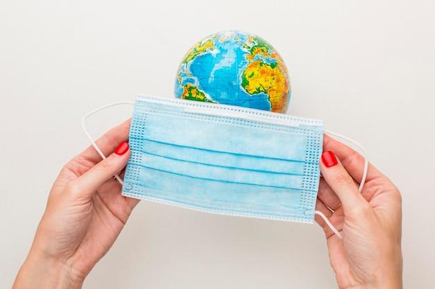 Bovenaanzicht van handen medische masker zetten earth globe