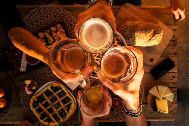 Bovenaanzicht van handen met bieren die juichen en samen plezier hebben