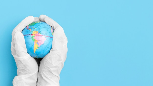 Bovenaanzicht van handen met chirurgische handschoenen met wereldbol met kopie ruimte