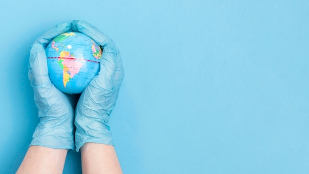 Bovenaanzicht van handen met chirurgische handschoenen met wereldbol