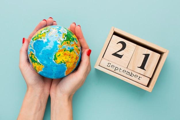 Bovenaanzicht van handen met earth globe met kalender