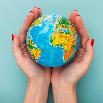Bovenaanzicht van handen met earth globe
