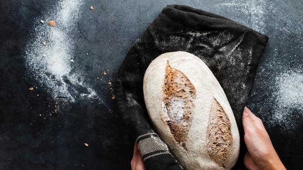 Bovenaanzicht van handen met een brood in doek