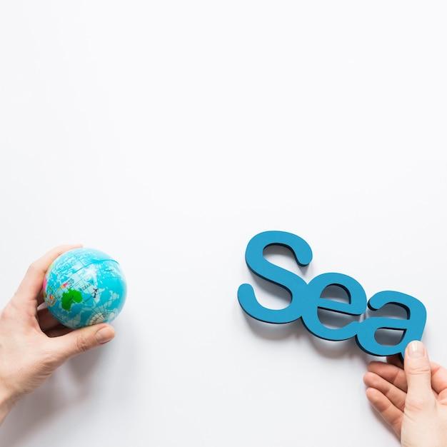 Bovenaanzicht van handen met globe en zee met kopie ruimte