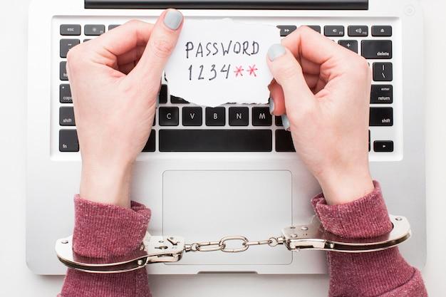 Bovenaanzicht van handen met handboeien met laptop wachtwoord