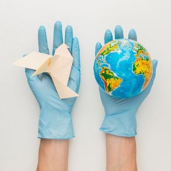 Bovenaanzicht van handen met handschoenen met duif en globe