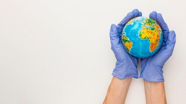 Bovenaanzicht van handen met handschoenen met earth globe