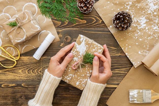 Bovenaanzicht van handen met kerstcadeau met plant en dennenappels