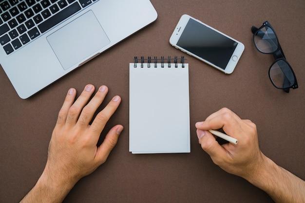Bovenaanzicht van handen met potlood en blanco notitieboekje