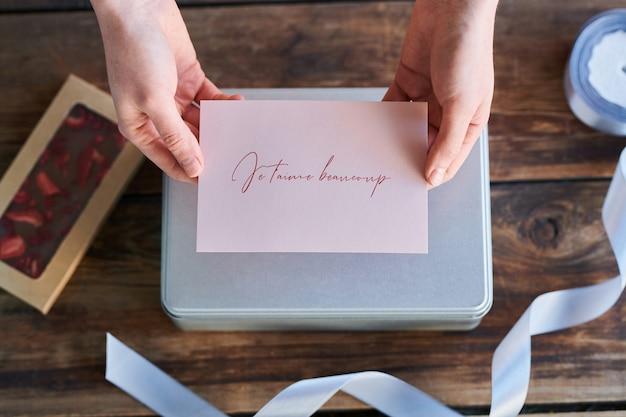Bovenaanzicht van handen met wenskaart met franse zin, wat betekent dat ik hou van je heel erg voorbereid op liefje