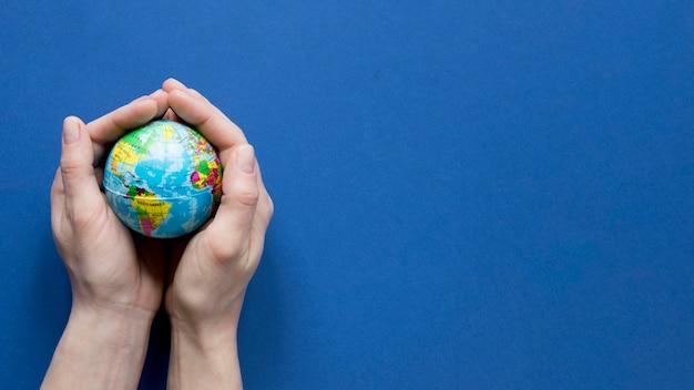 Bovenaanzicht van handen met wereldbol met kopie ruimte