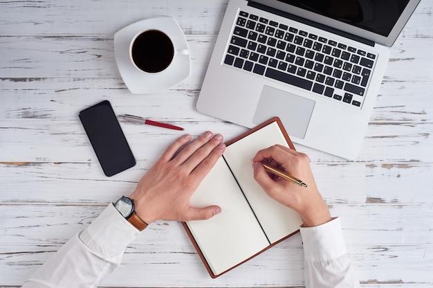 Bovenaanzicht van handen schrijven in kladblok, laptop, telefoon, pen en bril op tafel in kantoor.