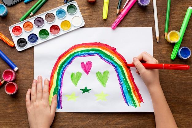 Bovenaanzicht van handen tekenen met markeringen en aquarel