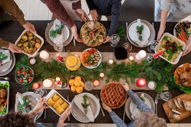 Bovenaanzicht van handen van familieleden die borden met zelfgemaakt eten en desserts vasthouden terwijl ze een feestelijke tafel serveren voor het kerstdiner