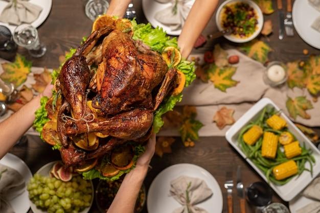 Bovenaanzicht van handen van jonge vrouw die geroosterde kalkoen doorgeeft aan haar man of ander familielid over een feestelijke tafel geserveerd met zelfgemaakt eten