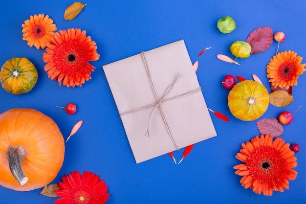 Bovenaanzicht van handgemaakte geschenkdoos met gele en oranje bloemen en pompoenen op blauwe ondergrond