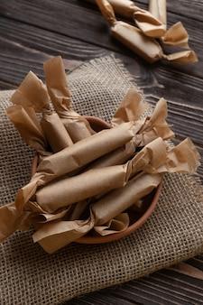 Bovenaanzicht van handgemaakte karamels verpakt in vetvrij papier op donker bord.