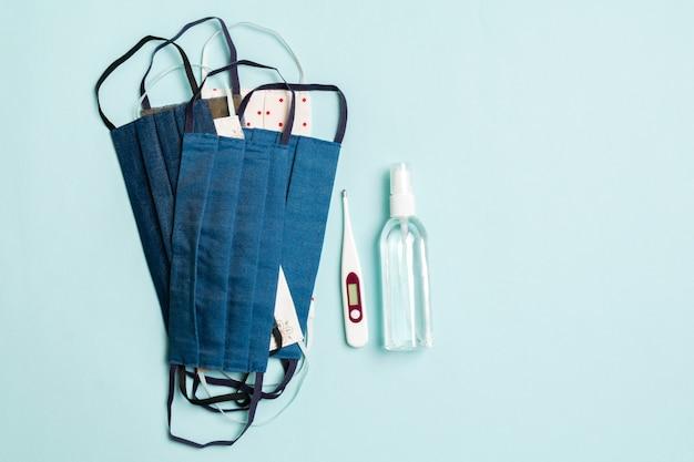Bovenaanzicht van handgemaakte katoenen maskers, digitale thermometer en alcoholgel-ontsmettingsmiddel op blauw.