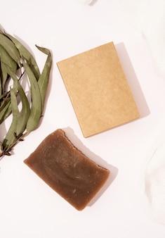 Bovenaanzicht van handgemaakte zeep en ambachtelijke doos met eucalyptusbladeren, mock-up ontwerp op witte achtergrond