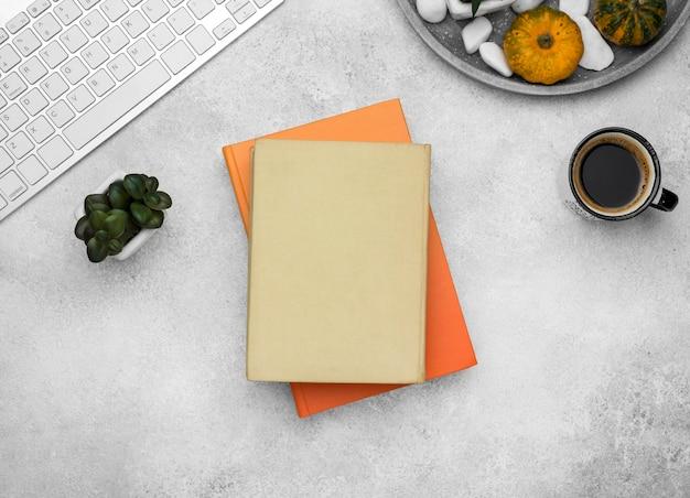 Bovenaanzicht van hardback boeken op bureau met koffie