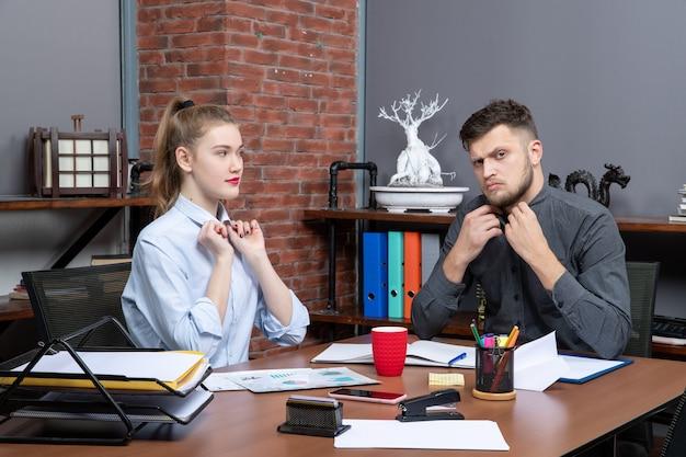 Bovenaanzicht van hardwerkend en zelfverzekerd professioneel team dat één belangrijk probleem op kantoor bespreekt