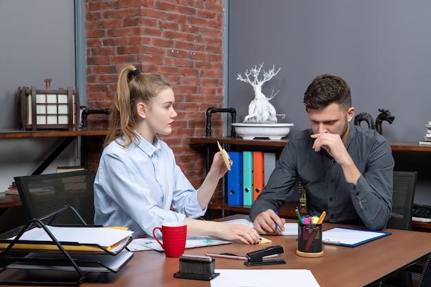 Bovenaanzicht van hardwerkende en gemotiveerde geschoolde werknemers die brainstormen over een belangrijk probleem op kantoor