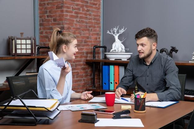 Bovenaanzicht van hardwerkende en zelfverzekerde potloodduwers die één belangrijk probleem op kantoor bespreken