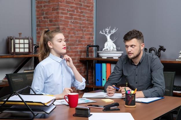 Bovenaanzicht van hardwerkende jonge man en vrouwelijke collega die één probleem bespreken in een kantooromgeving