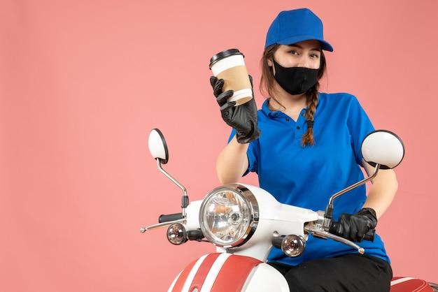 Bovenaanzicht van hardwerkende vrouwelijke koerier met een zwart medisch masker en handschoenen die bestellingen afleveren op perzikachtergrond