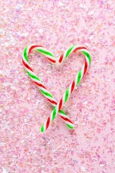 Bovenaanzicht van hart gemaakt van twee lollies op roze met glitter