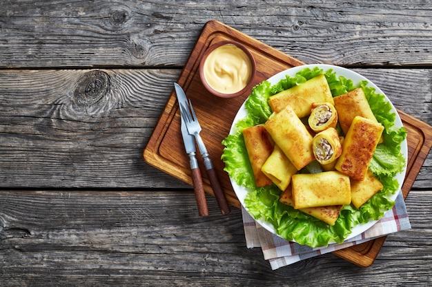 Bovenaanzicht van hartige crêpe broodjes met gemalen kippenvlees en champignonvulling geserveerd op een bedje van verse slablaadjes op een witte plaat