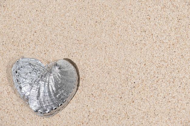 Bovenaanzicht van hartvorm zilveren kleur zeeschelp op zand achtergrond met kopie ruimte