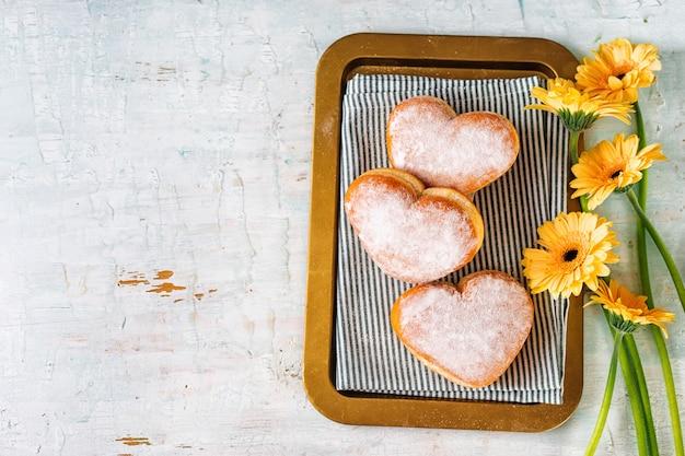Bovenaanzicht van hartvormige donuts in een lade met bloemen