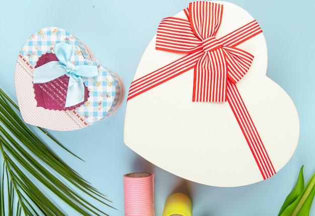 Bovenaanzicht van hartvormige geschenkdozen en rollen plakband op blauwe achtergrond