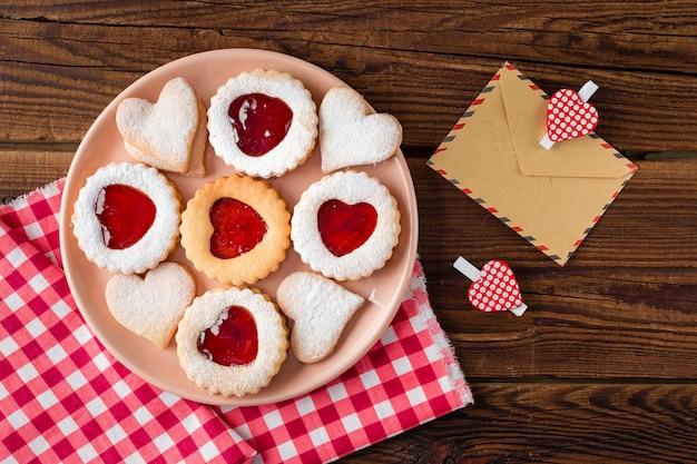 Bovenaanzicht van hartvormige koekjes op plaat met jam