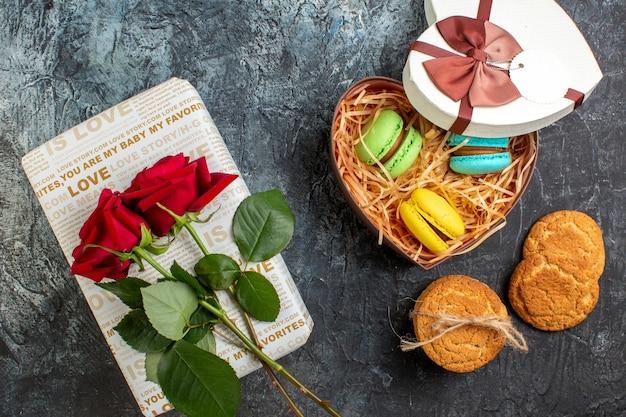 Bovenaanzicht van hartvormige mooie geschenkdoos met heerlijke macarons en koekjes rode roos op ijzige donkere achtergrond