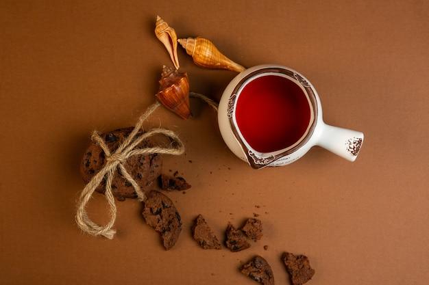Bovenaanzicht van havermout koekjes met chocoladeschilfers vallende gebroken schelpen en een kopje thee op oker