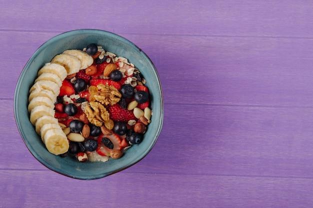 Bovenaanzicht van havermoutpap met aardbeien, bosbessen, bananen, gedroogd fruit en noten in een keramische kom op paarse houten oppervlak met kopie ruimte