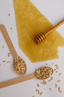 Bovenaanzicht van havervlokken en honing. gezonde voedingsingrediënten, natuurlijke gezondheidsproducten